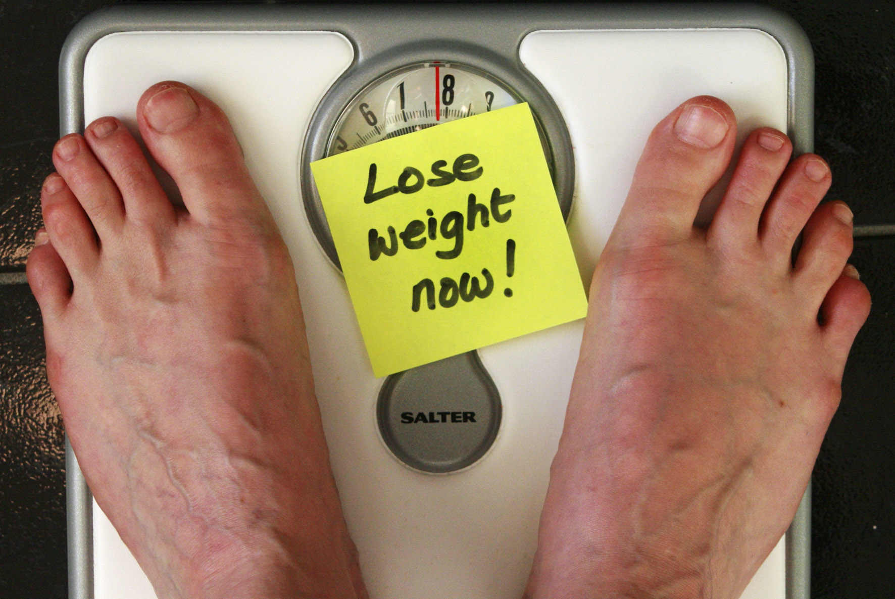 "man's feet standing on a weighing scale with a yellow post-it with the words ""lose weight now!"" on it, weight loss, intermittent fasting, dieting"