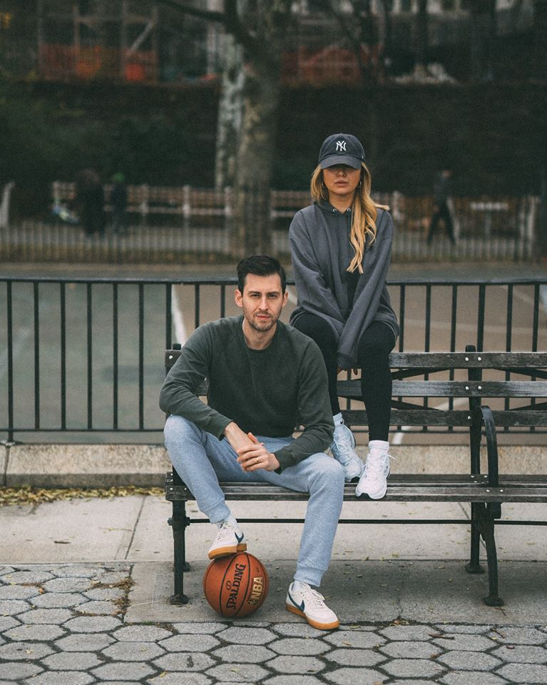 man with a basketball and a woman sitting on a bench modeling hanes athleisure