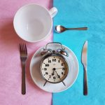 cutlery with an alarm clock on the plate against a pink and blue background, intermittent fasting, timed meals