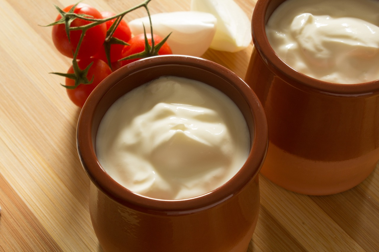 two ceramic jars of white cream on a wooden table with tomatoes and onion slices, homemade conditioner ingredients