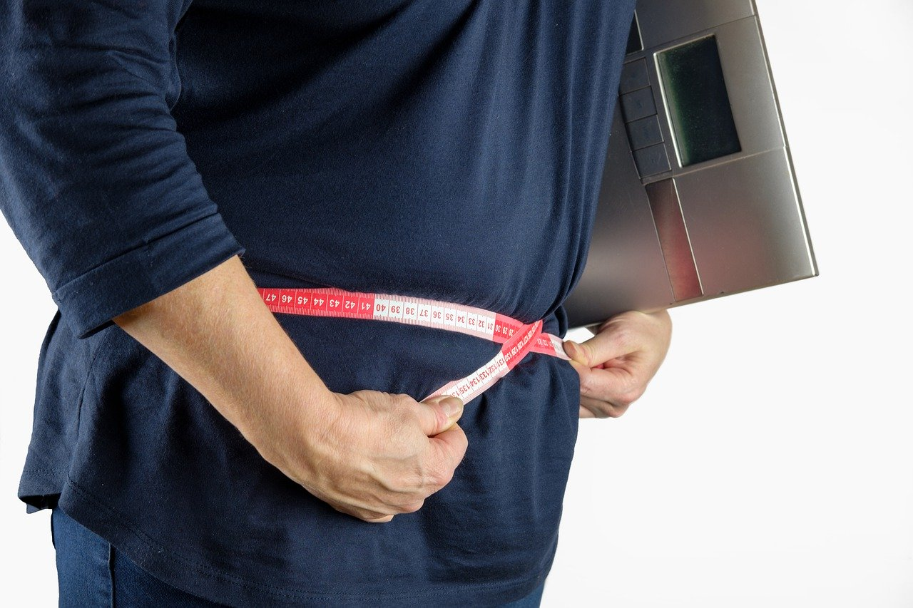 person carrying a weighing scale and measuring their waist with a tape measure, fat, health measurement