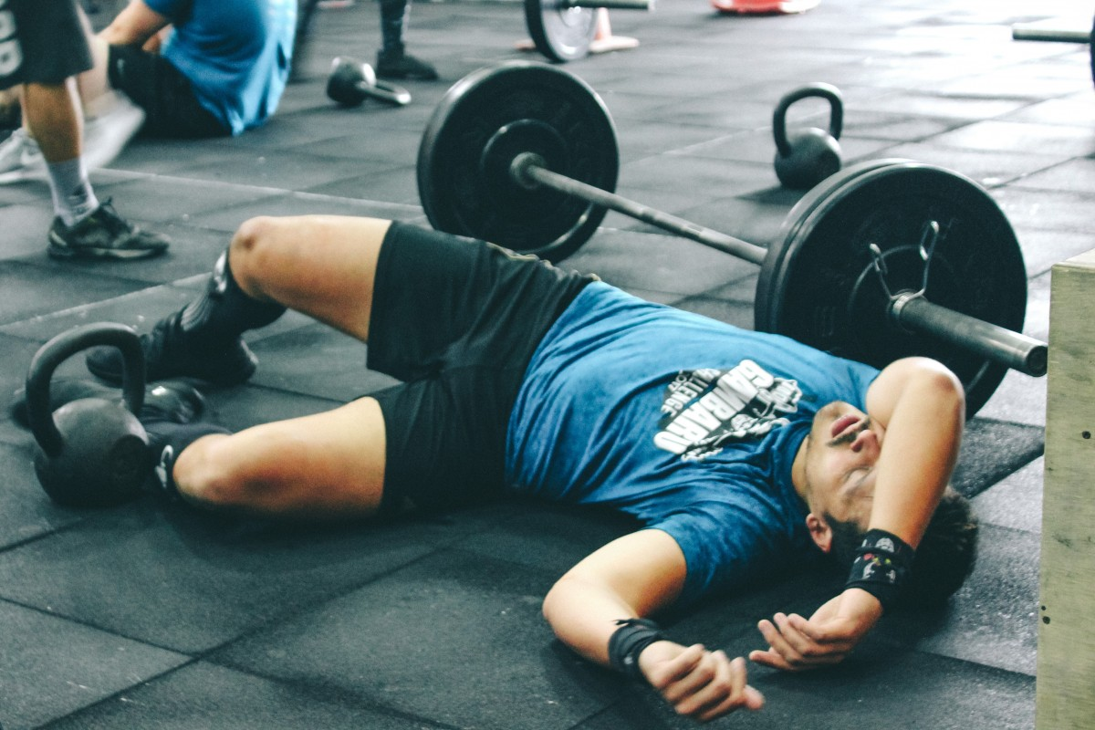 exhausted man lying on the floor next to a barbell in the gym, no energy, tired, fainting, exercise