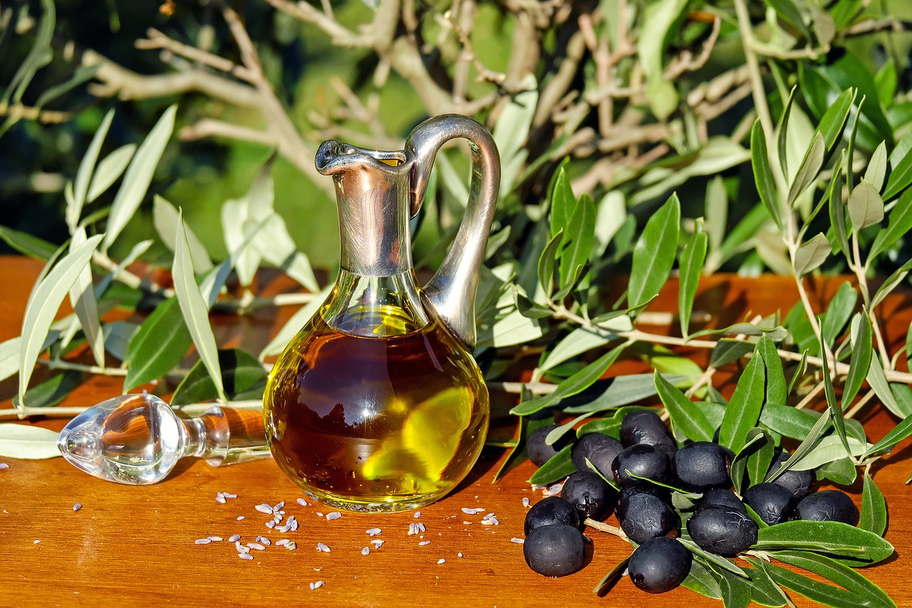 olive oil in a glass flask with olive branches in the sunlight, homemade conditioner ingredients