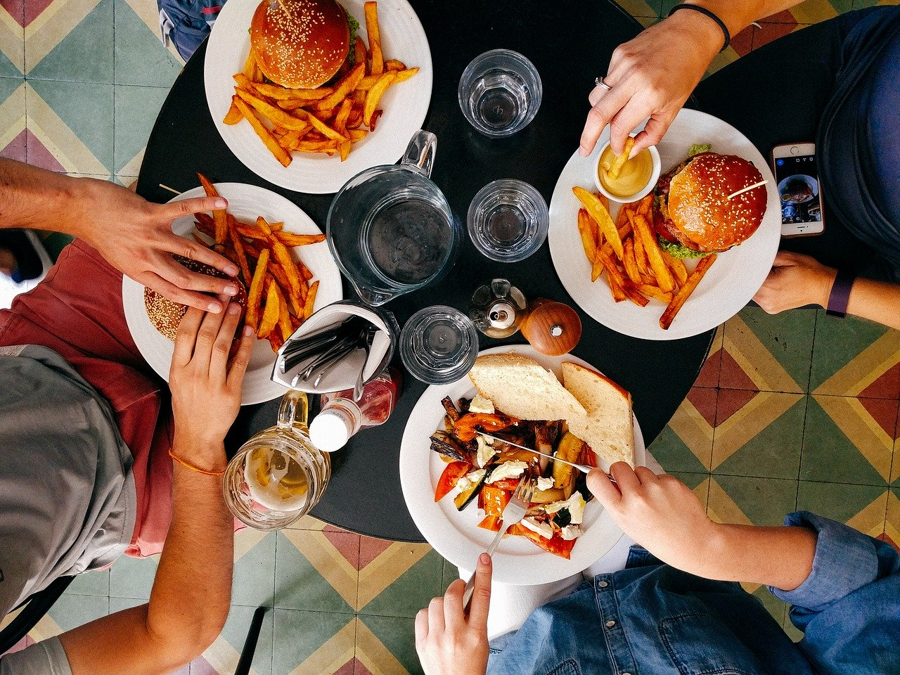 top view of a group of friends eating around a table, fast food, unhealthy eating, overeat, diet