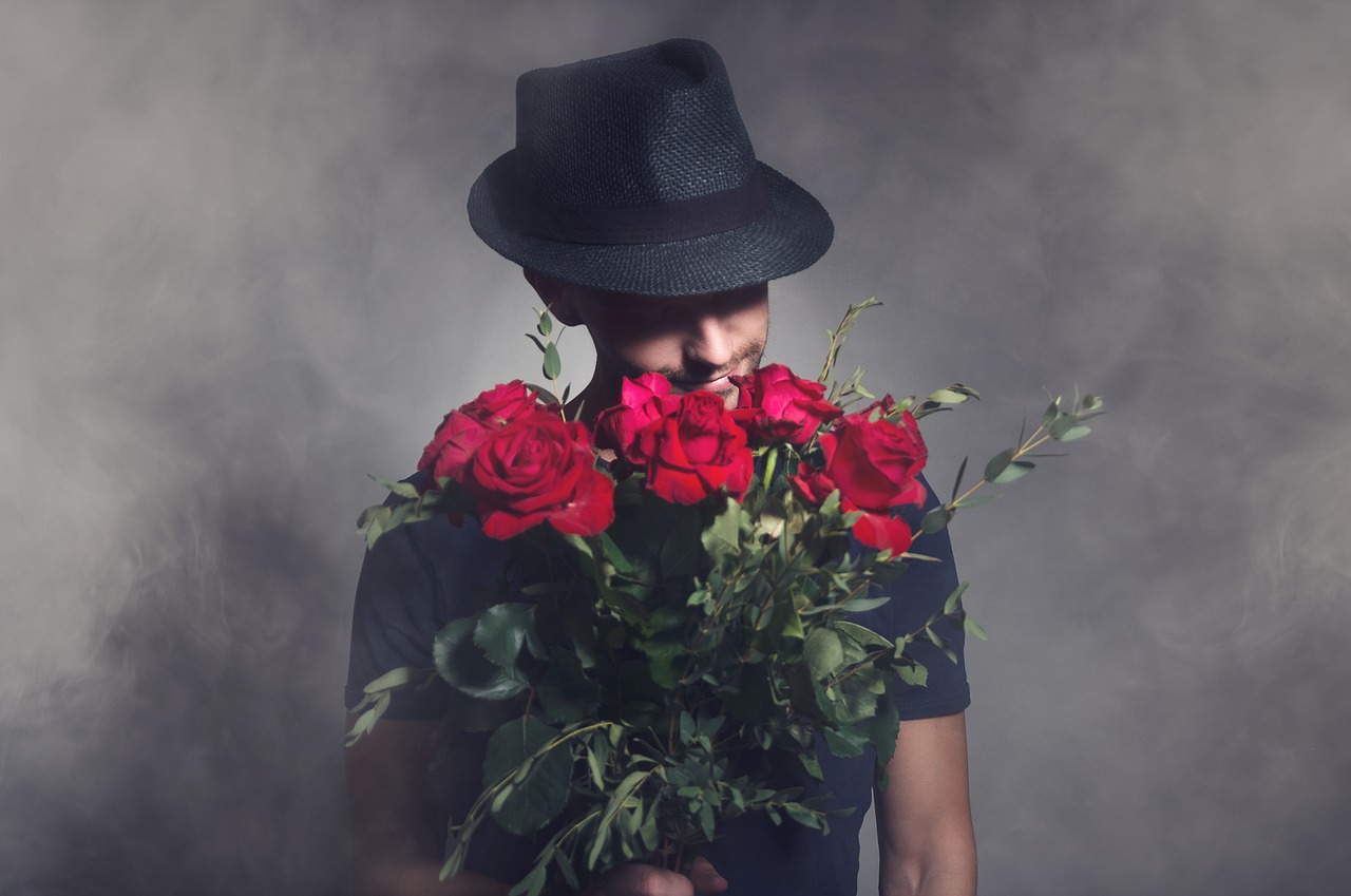 man in a black shirt and black fedora holding a bouquet of roses, romantic, flowers, dating profile stereotypes