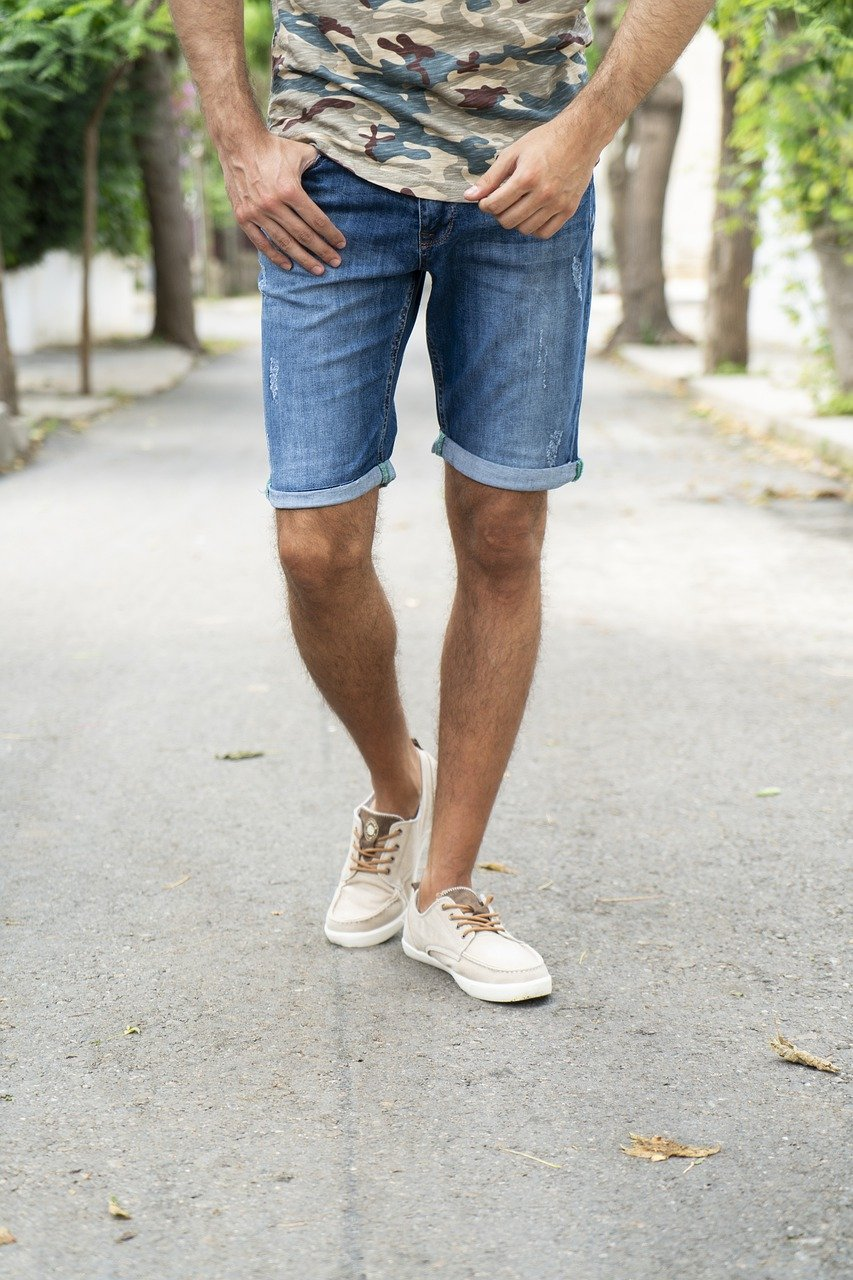 half shot of a man wearing a camo top, denim shorts and white sneakers, casual fashion, casual outfits, casual clothes, casual wear
