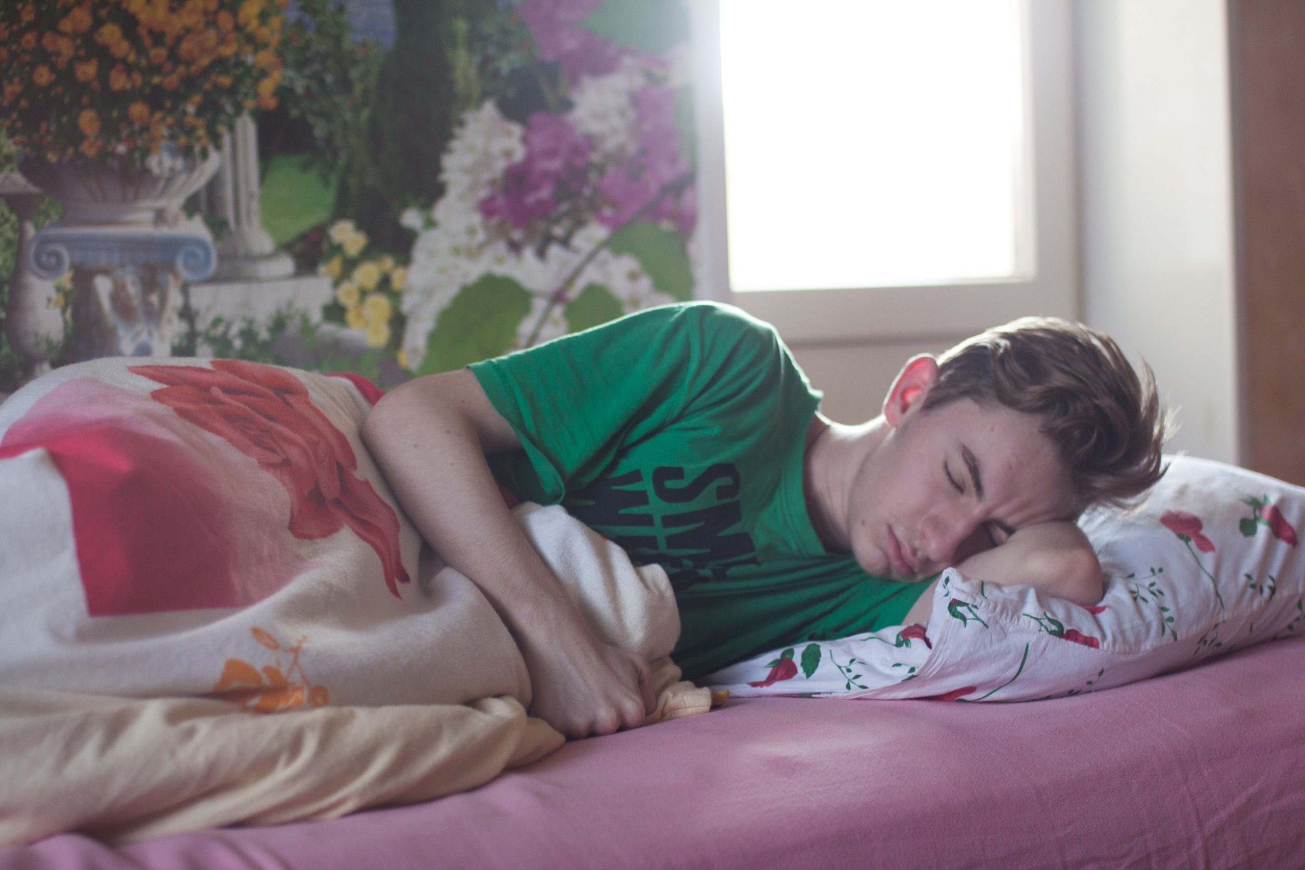 man in a green shirt sleeping in bed with a floral print, rem sleep