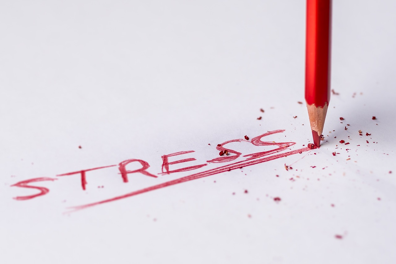 "the word ""stress"" written in a red colored pencil with its tip being crushed on the paper, increased cortisol levels"