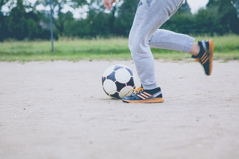 person's legs wearing sweatpants playing soccer on sandy ground, athleisure basics