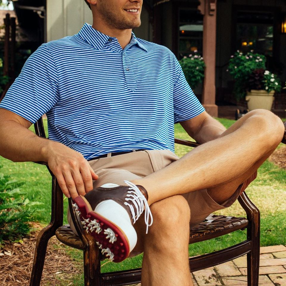half shot of a man sitting in a chair and modeling tasc performance's golf athleisure attire, athleisure brands