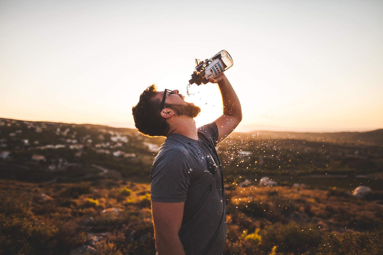 man pouring water in his mouth against the sun, thirsty, dehydration, drink water