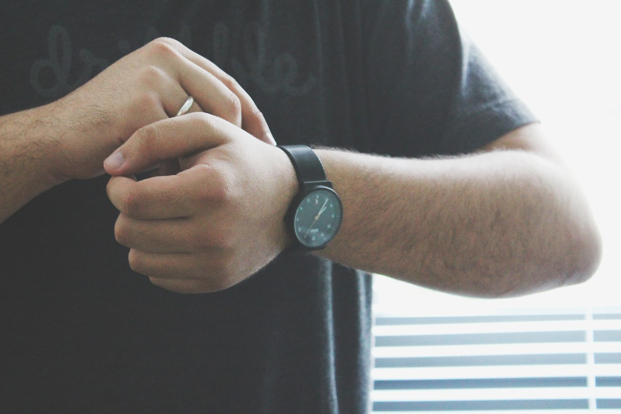 man in a black shirt putting on a watch, how to wear a watch, which hand do you wear a watch on