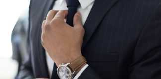 focus shot of a man wearing a suit and fixing his tie while showing off his watch