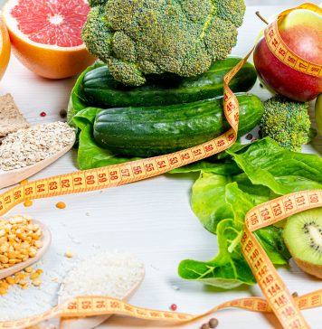Fresh Fruits, Vegetables, Cereals and Grains on A White Surface with A Measuring Tape Around Them
