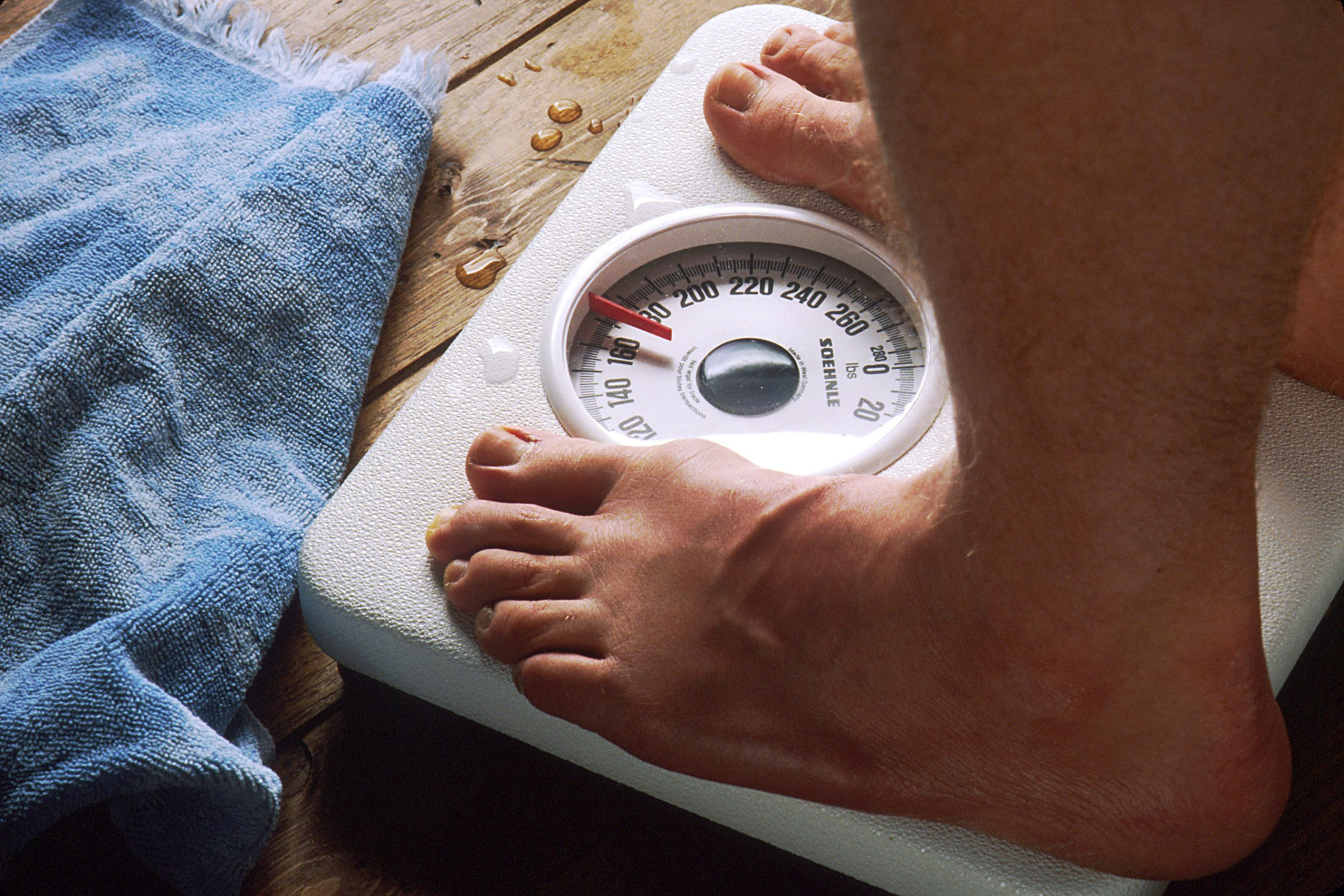 man's feet standing on a bathroom scale with a blue towel on the floor, weight, bmi, health