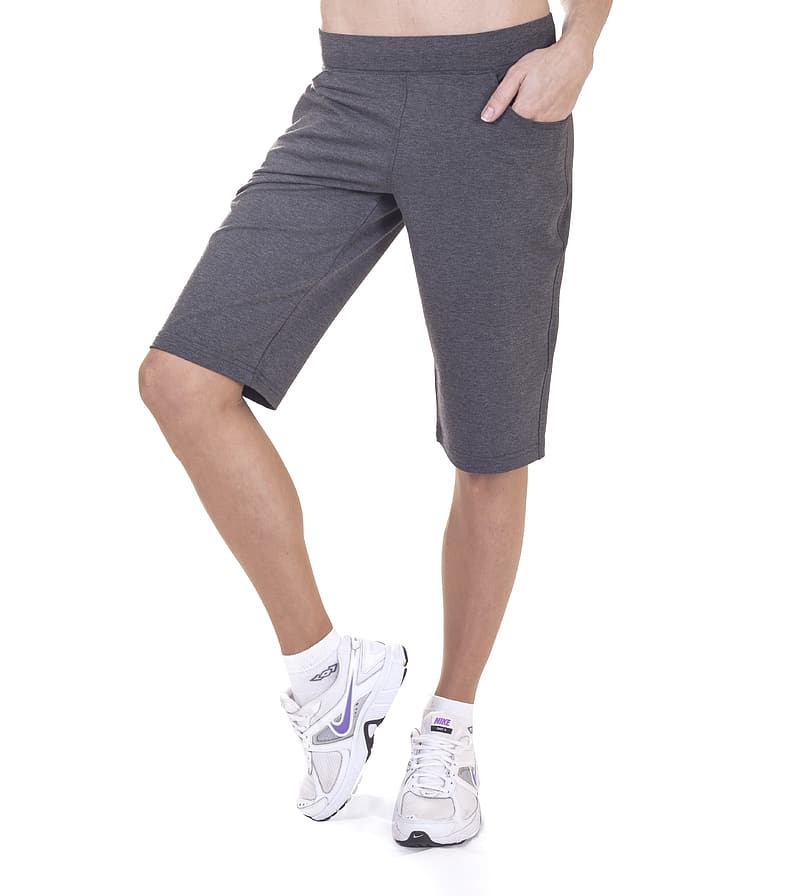 half shot of a model wearing dark gray workout shorts and white sneakers, athleisure basics