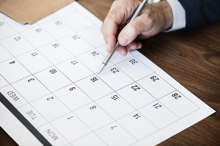 man's hand pointing to a calendar with a pen