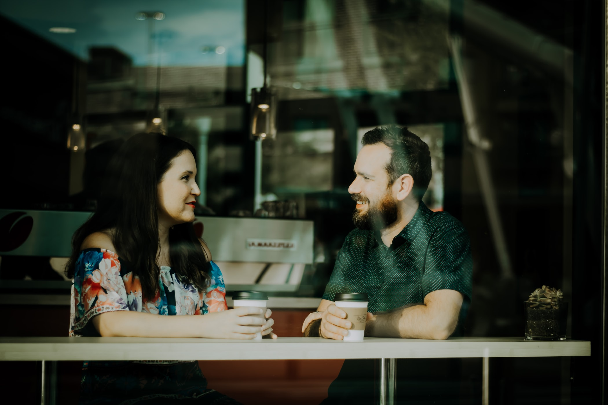 couple sitting at a cafe window and looking at each other