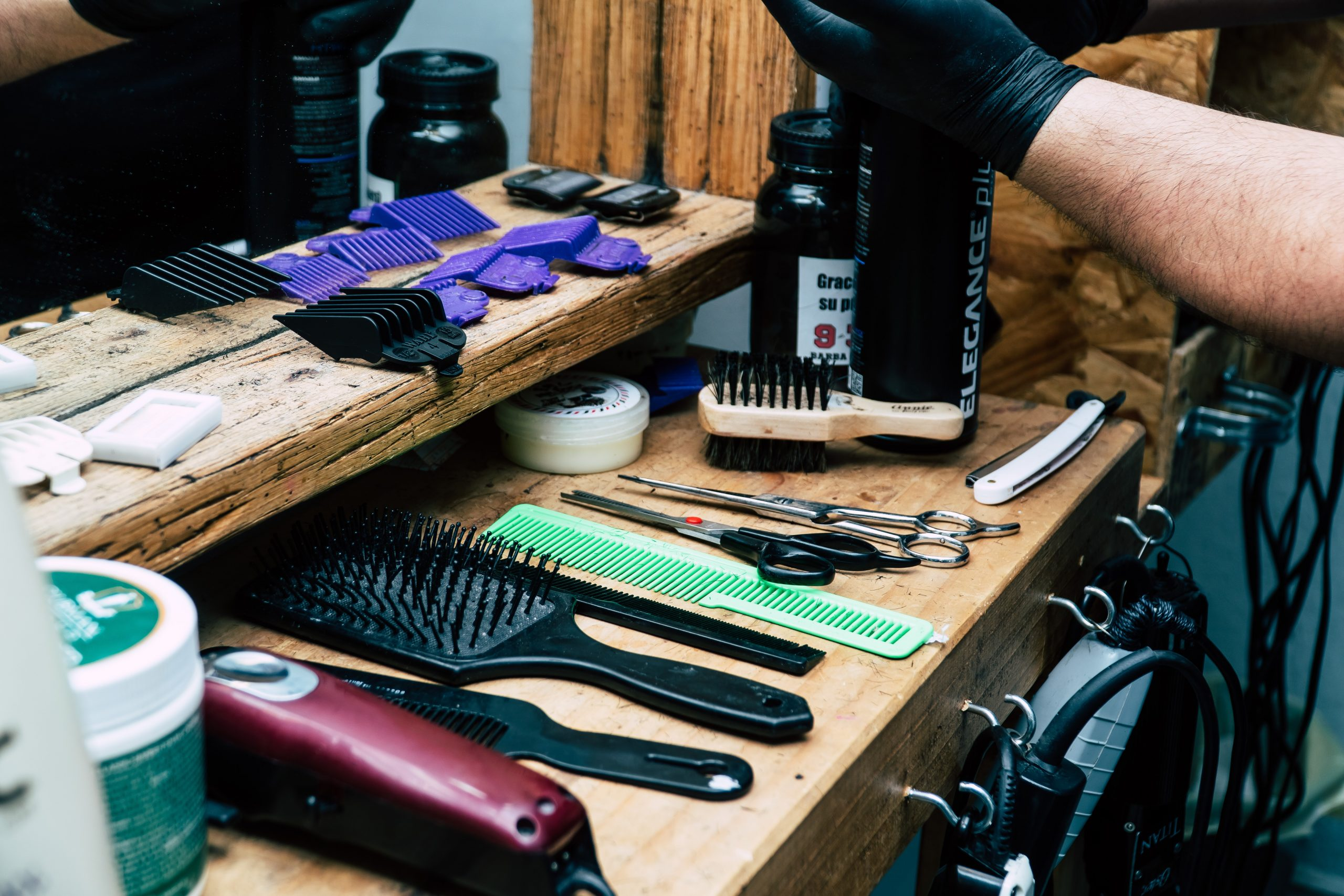 tools for hair styling and cutting laid out on a wooden dressing table