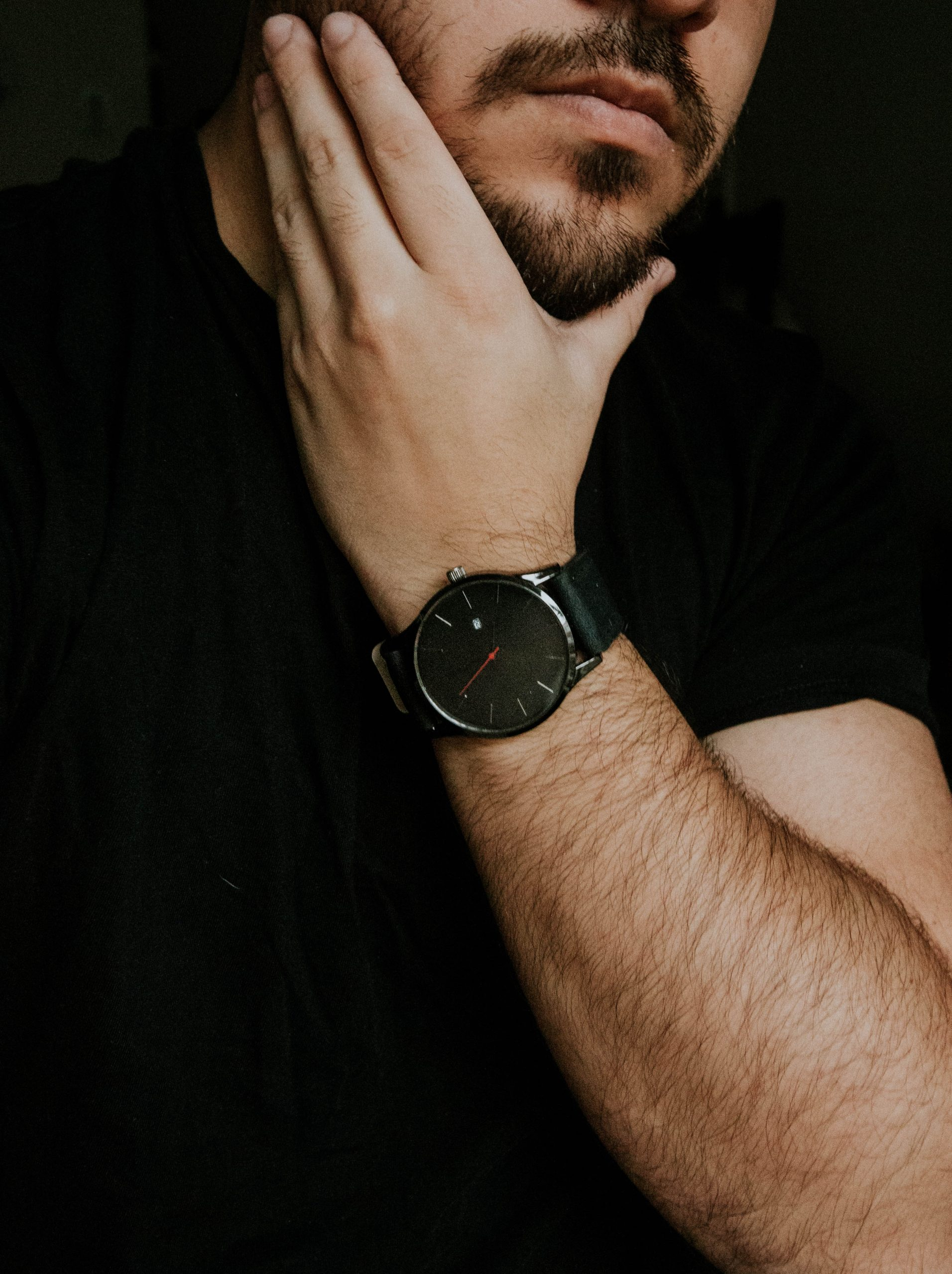 bearded man holding his chin