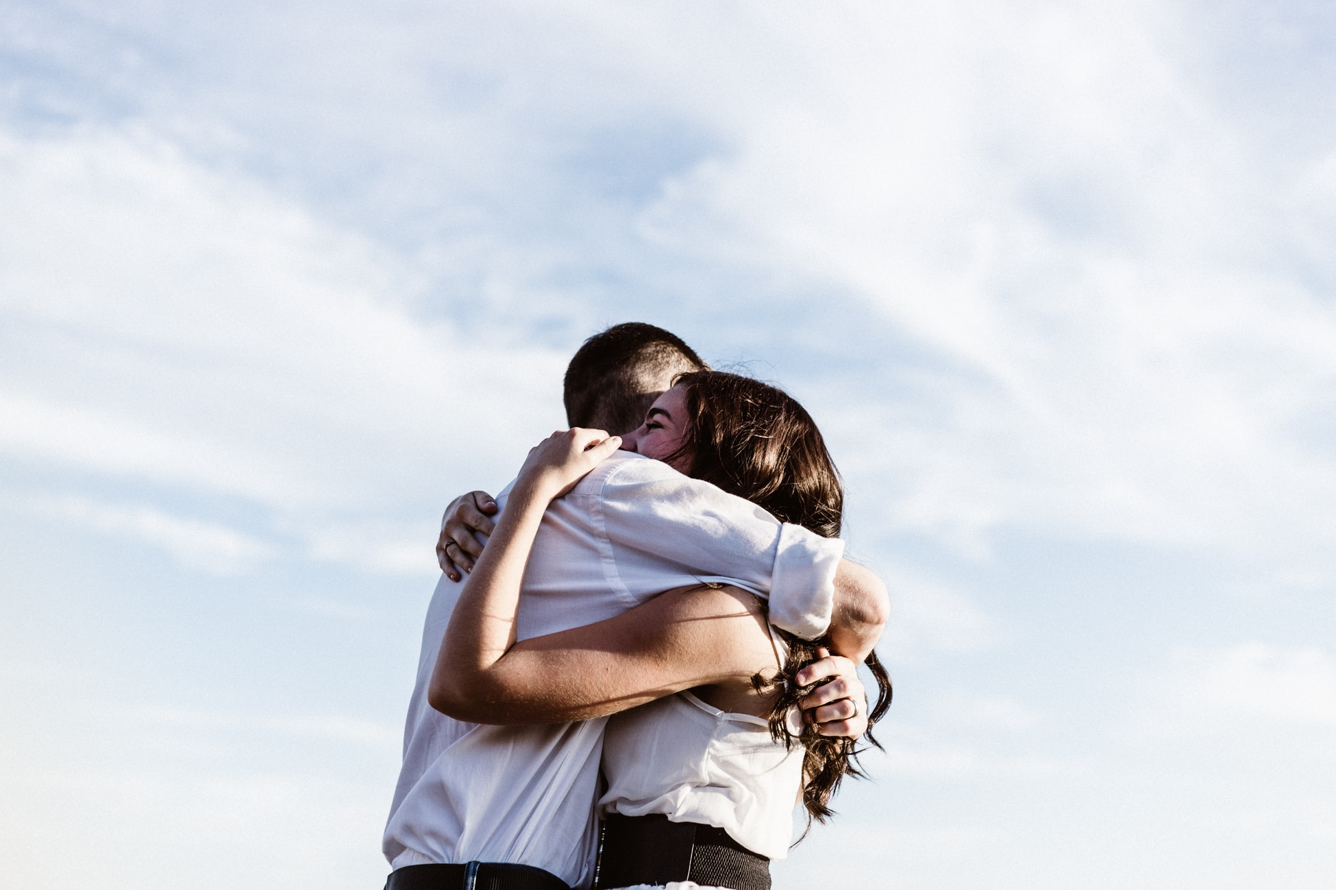 happy couple in a tight embrace against a big open blue sky