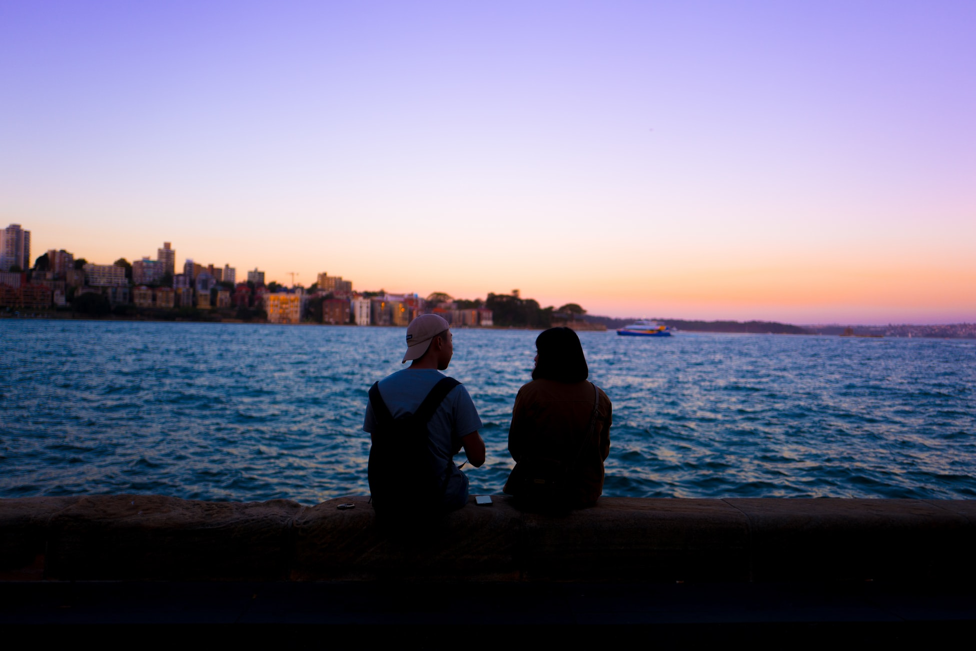 couple sitting by the water watching the sunset