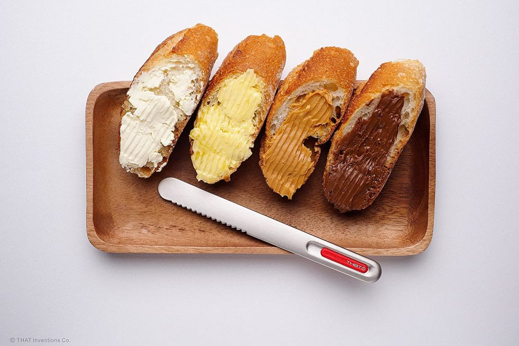 Butter knife and 4 slices of bread with different spreads on them