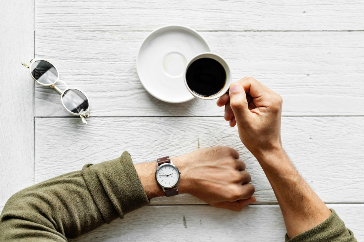 top view of a man looking at his watch as he drinks coffee