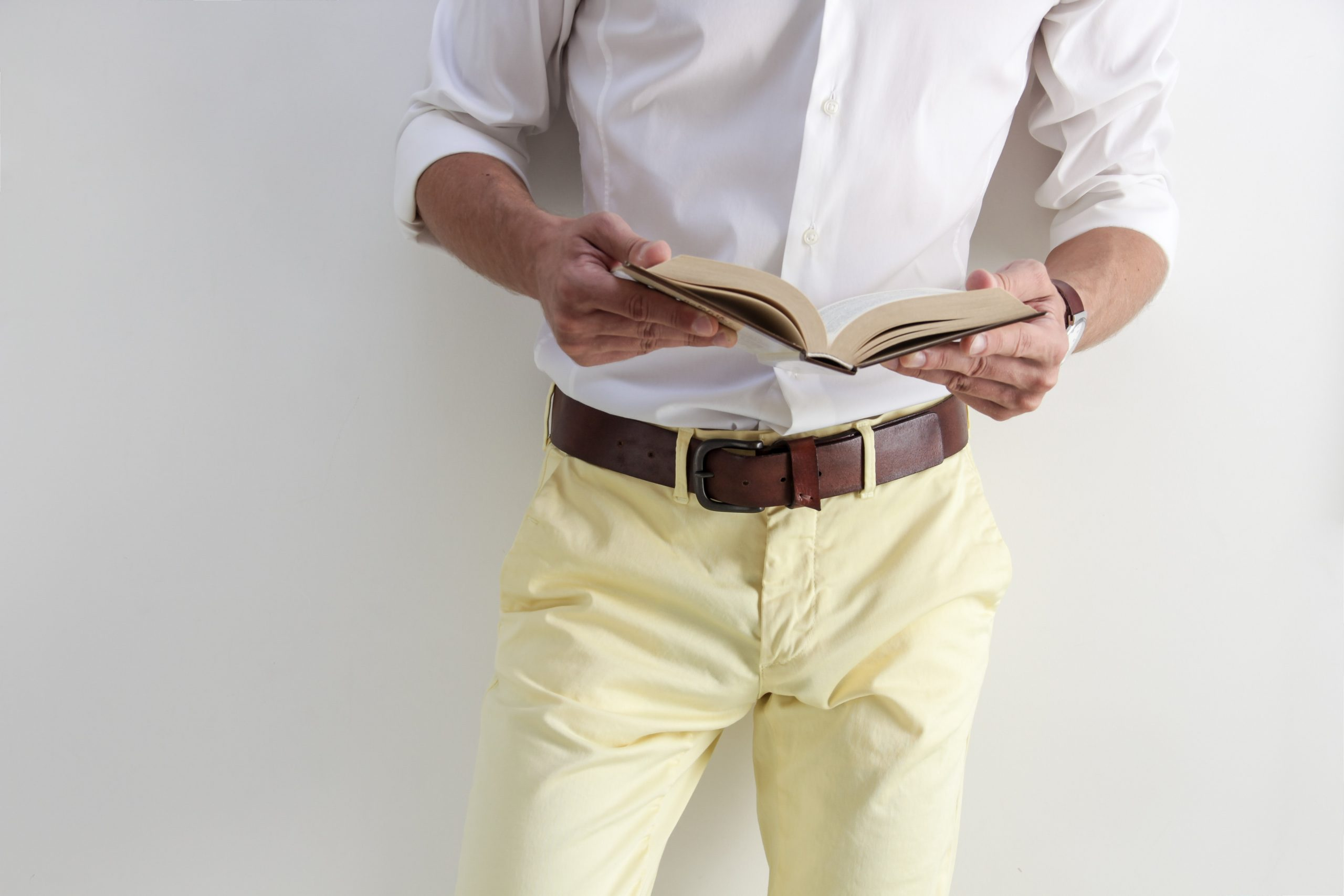 torso shot of a man wearing a white dress shirt and light yellow pants, business casual attire