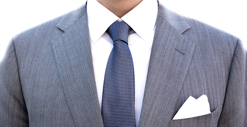 upper torso shot of a man in a gray suit, dark tie, white collared shirt and a white pocket square, business formal attire