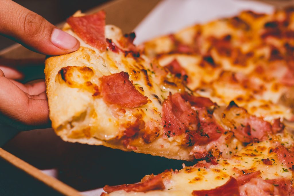 close-up-photo-of-person-holding-pizza-1653877