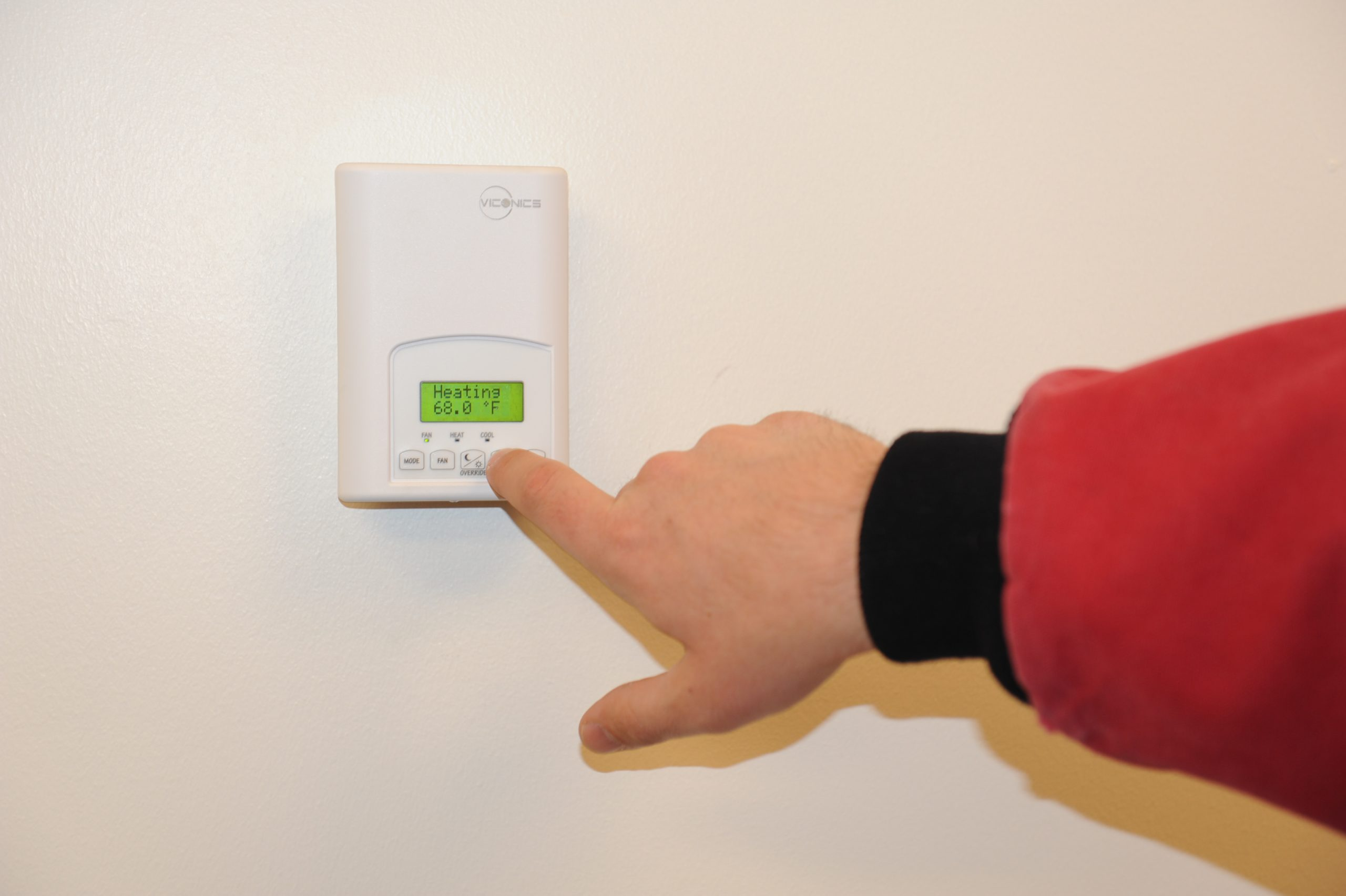 person's hand lowering the wall thermostat