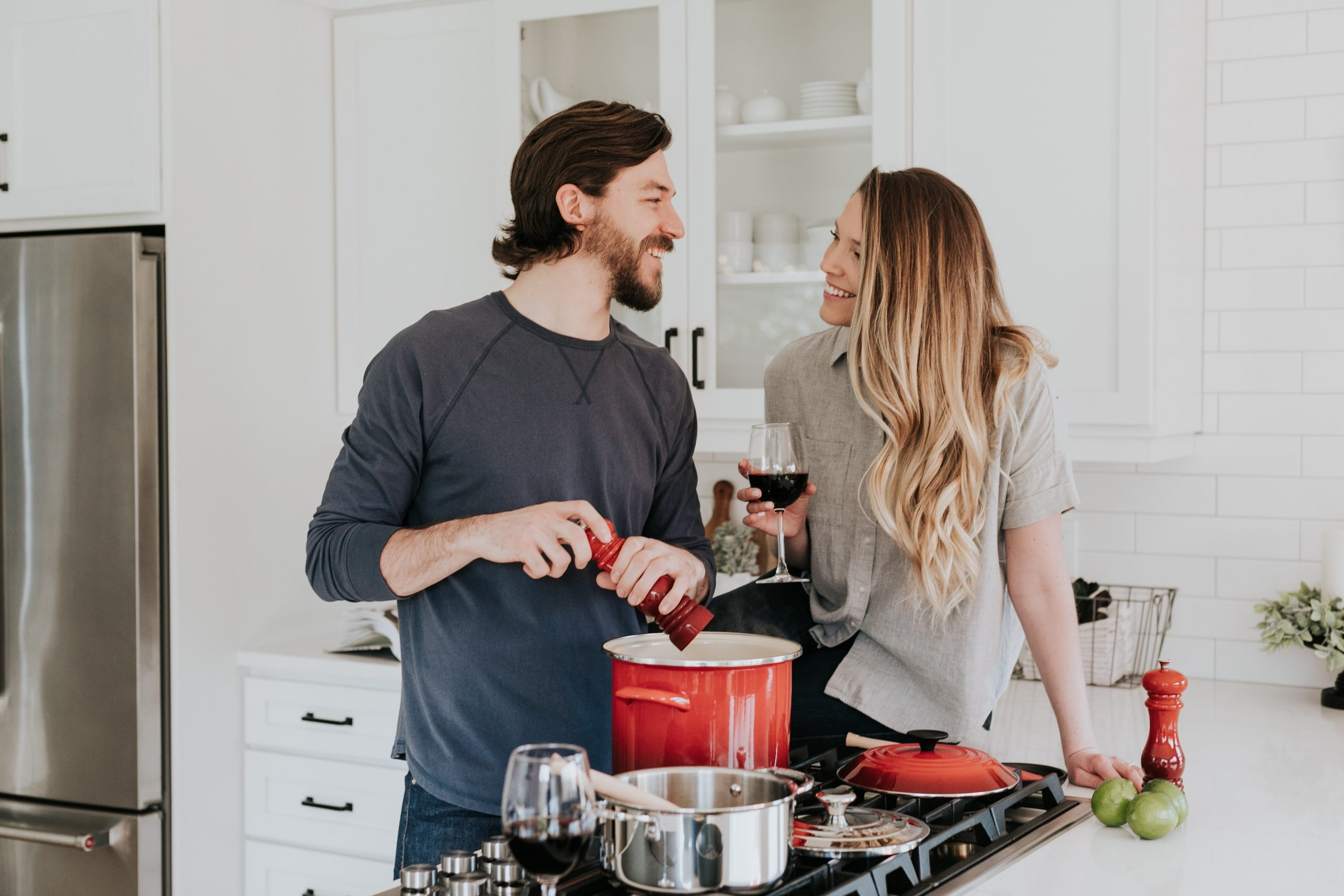 couple looking at each other lovingly as the man is cooking a meal on the stove