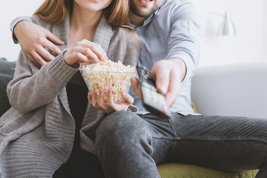couple seated on a couch watching a movie on the tv with a bowl of popcorn