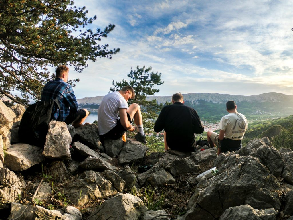four-men-seated-on-rocks-facing-mountain-1070492_