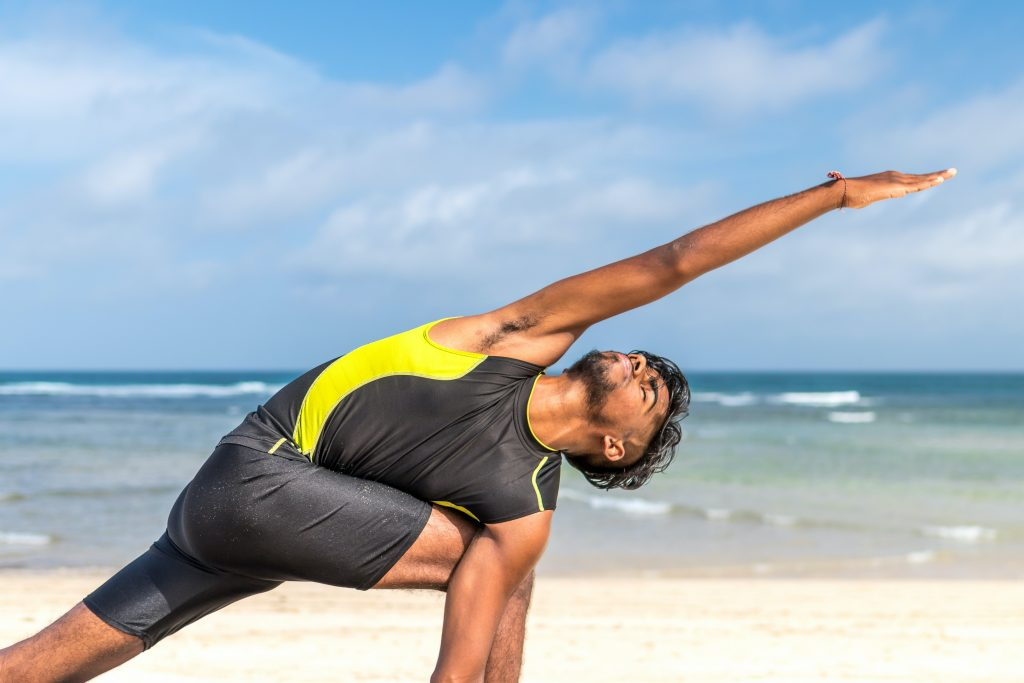 man-in-yellow-and-black-tank-top-doing-exercise-on-seashore-616999_