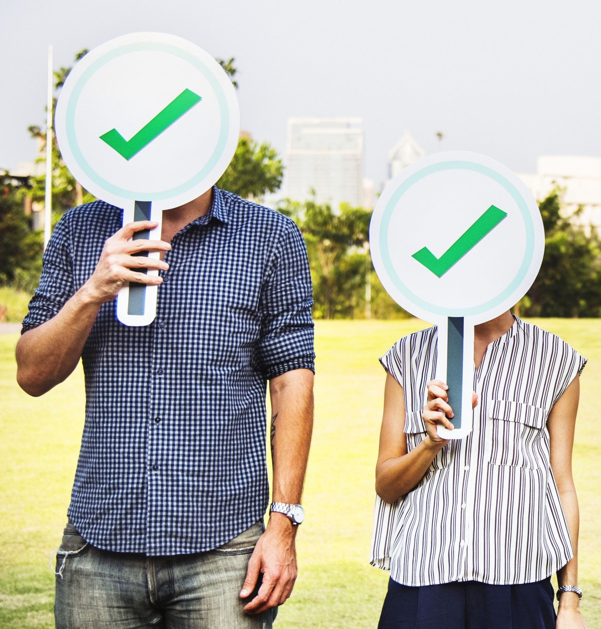 man and woman standing in a field holding checkmark signs in front of their faces