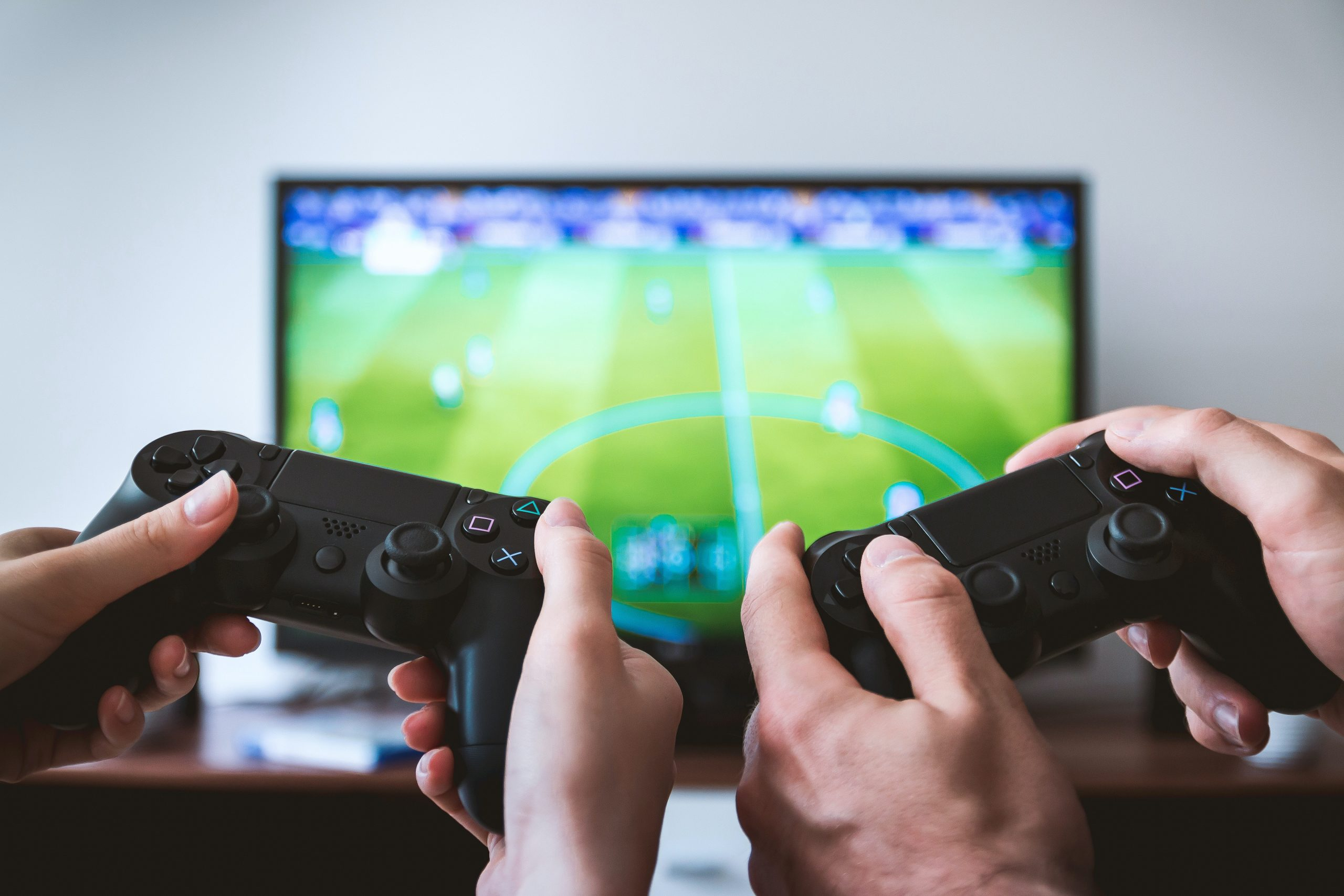 two people holding game consoles playing a video game