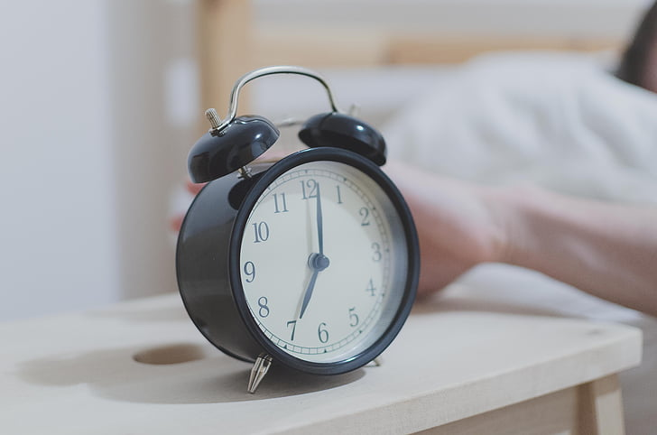 alarm clock on a bedside table and a person lying in the bed next to it reaching out towards the clock, sleep routine