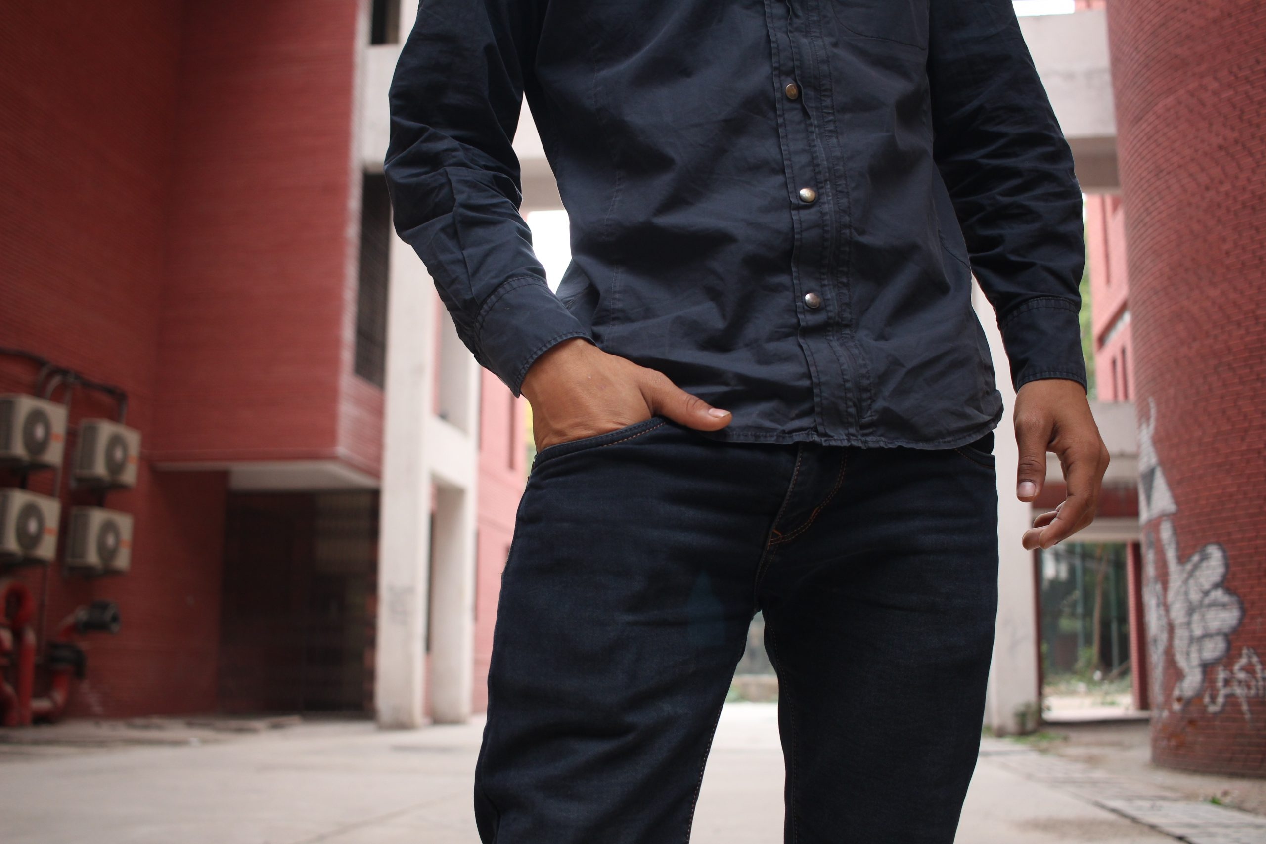 torso shot of a man wearing a dark long-sleeved buttoned shirt and dark jeans, smart casual attire