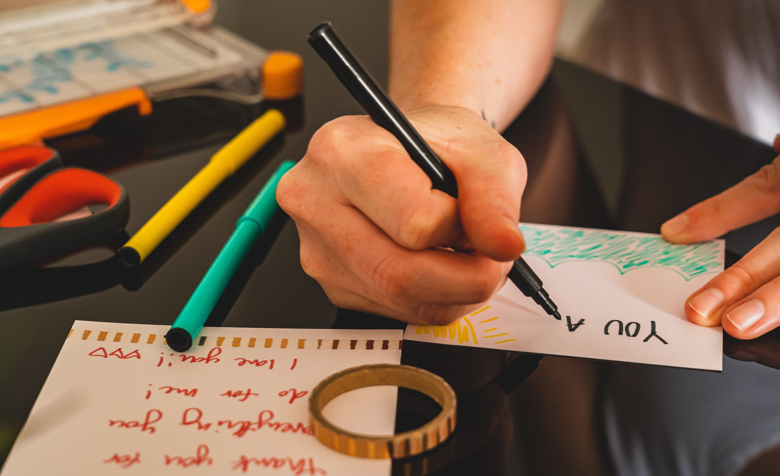 person writing and drawing on a card with colored markers