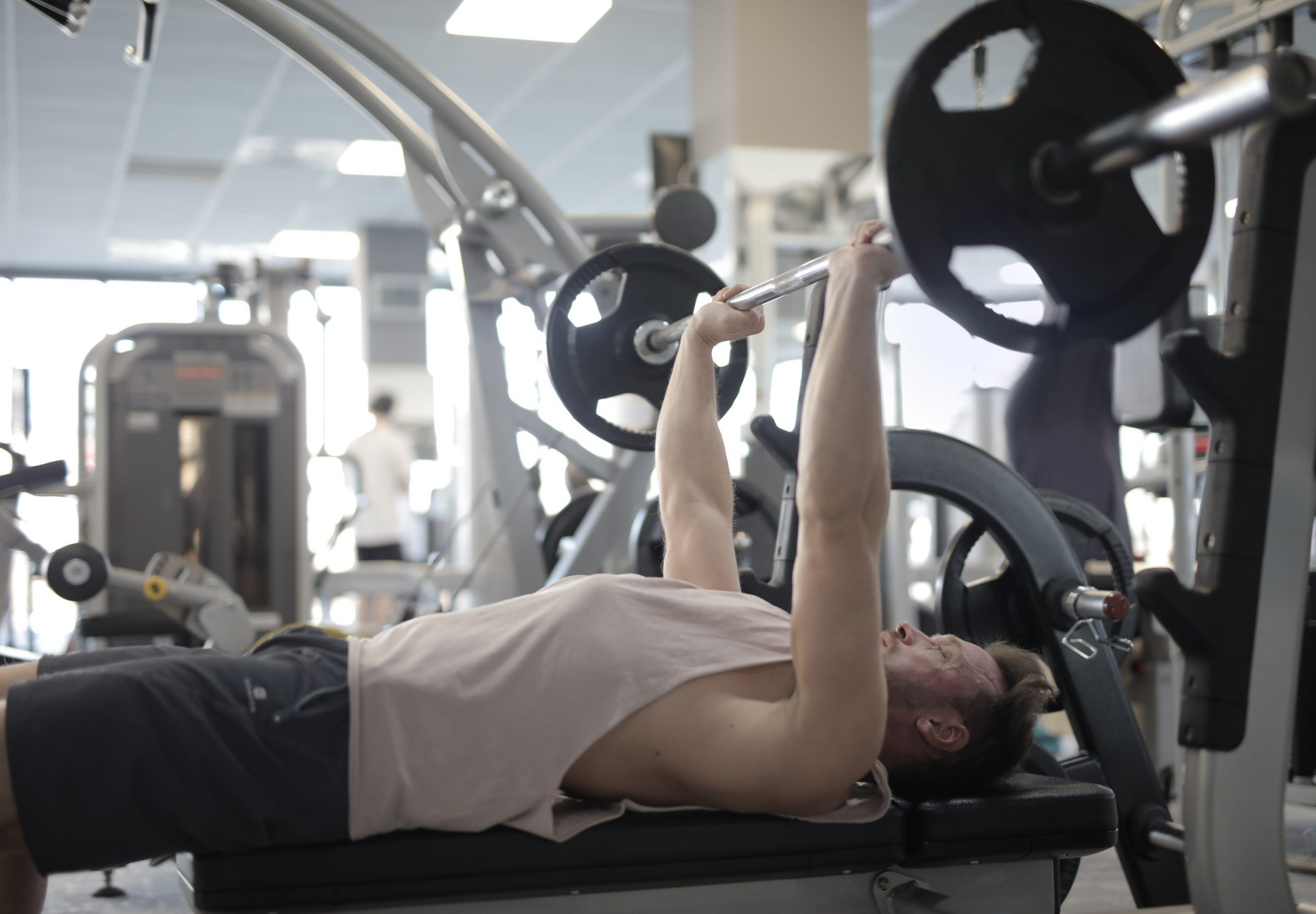 muscular man lifting up free weights in a gym