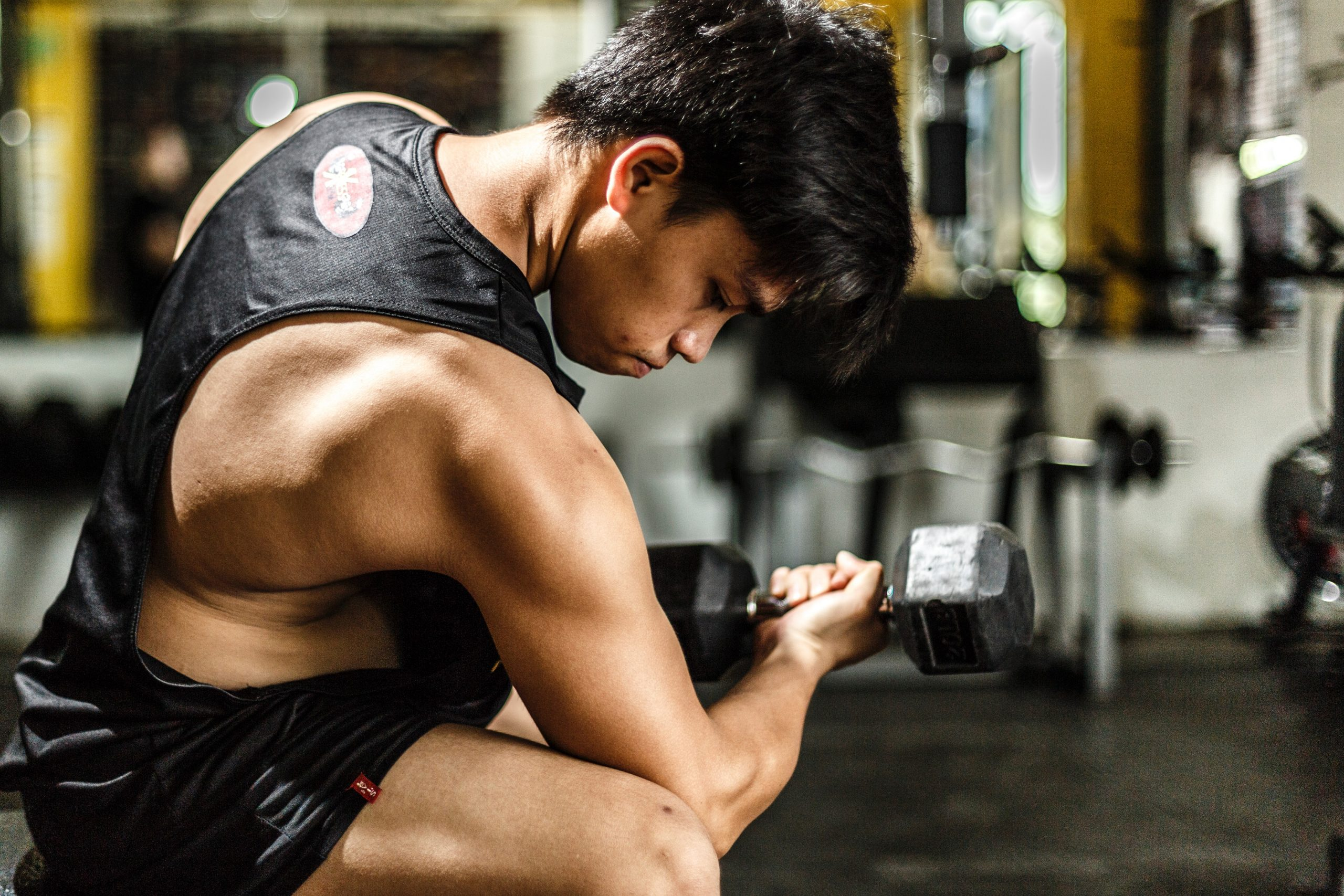man wearing a black tank top working out with best gym weights