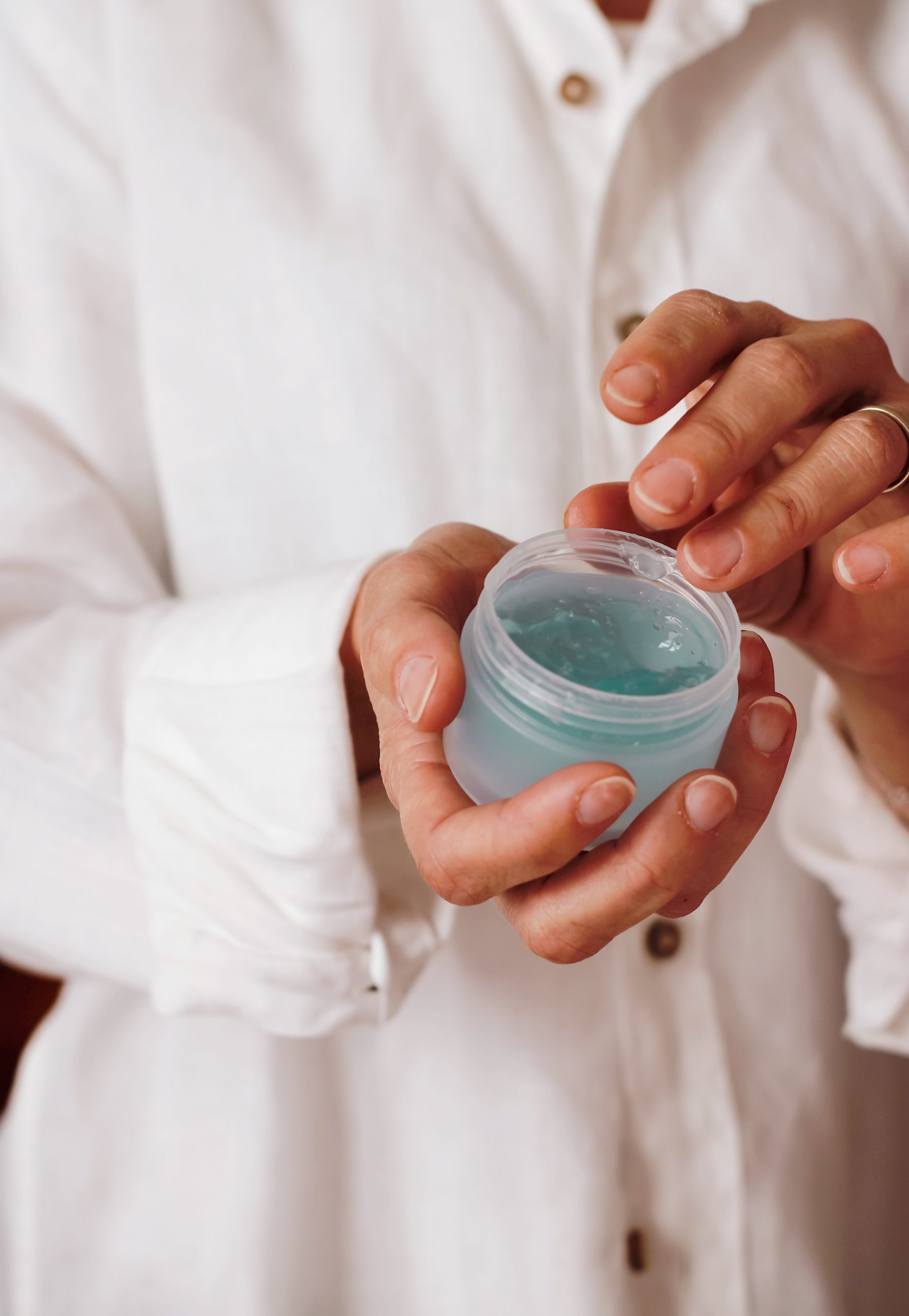 person holding a container of aloe vera gel after male eyebrow threading