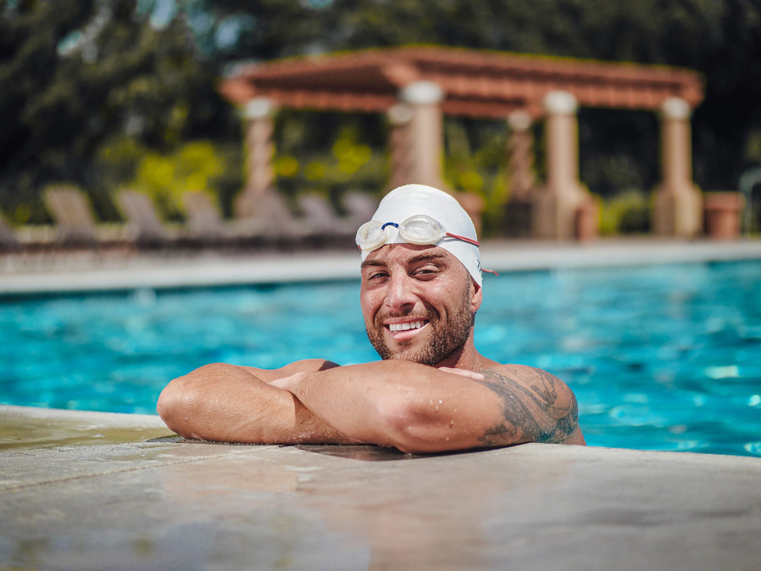 an wearing a white cap and staying at the edge of a swimming pool