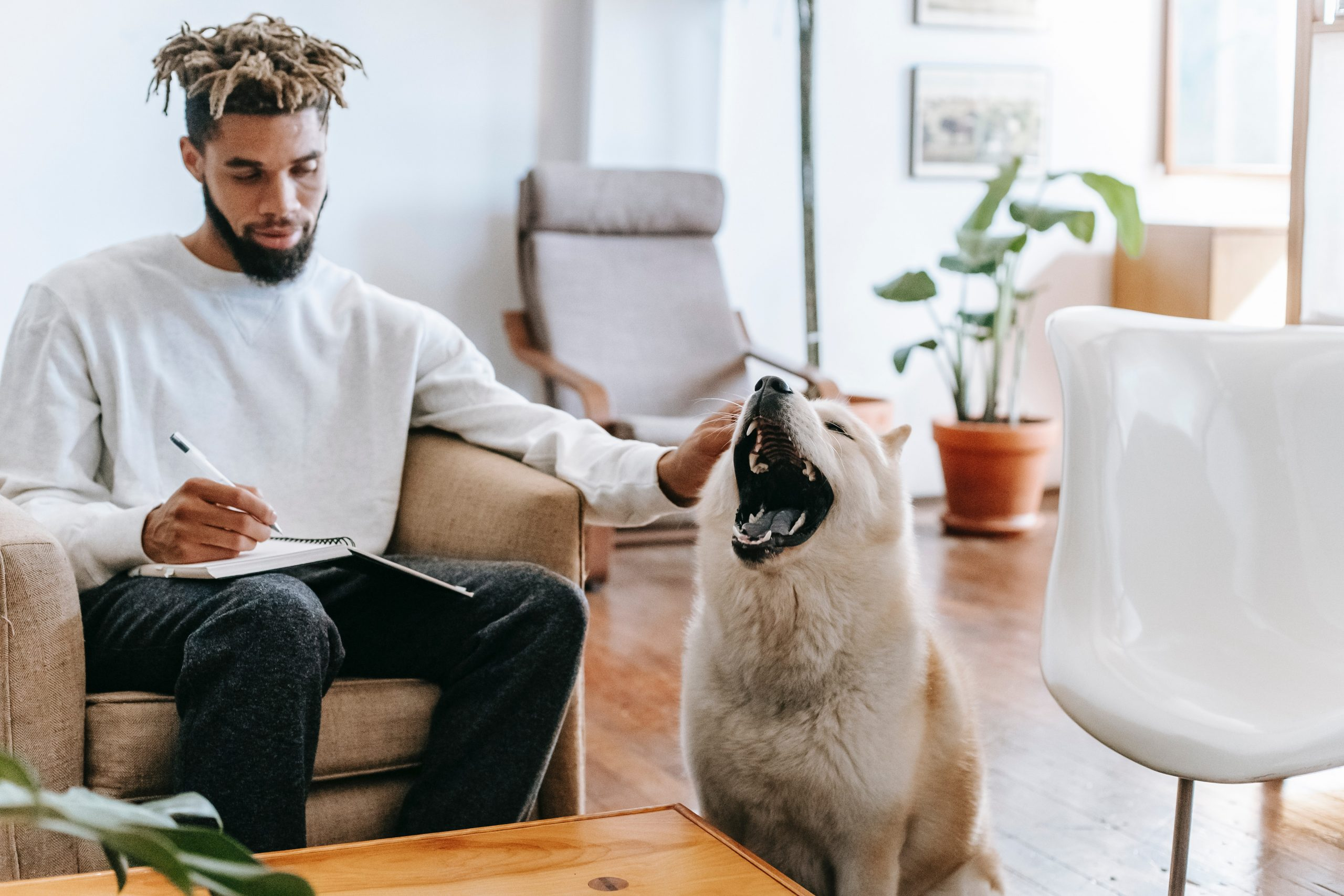 man taking note of his napping schedule in notebook while petting his dog
