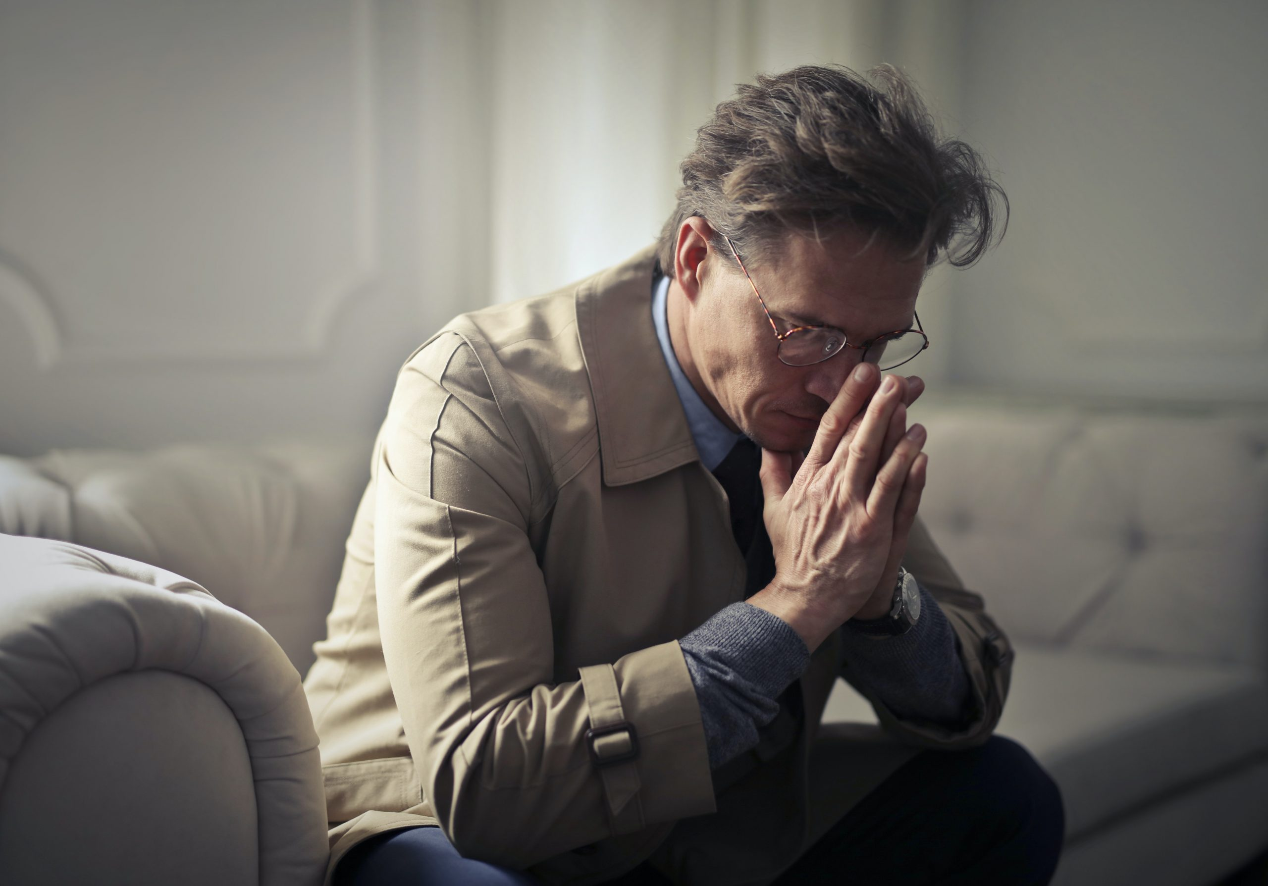 worried man sitting on the couch