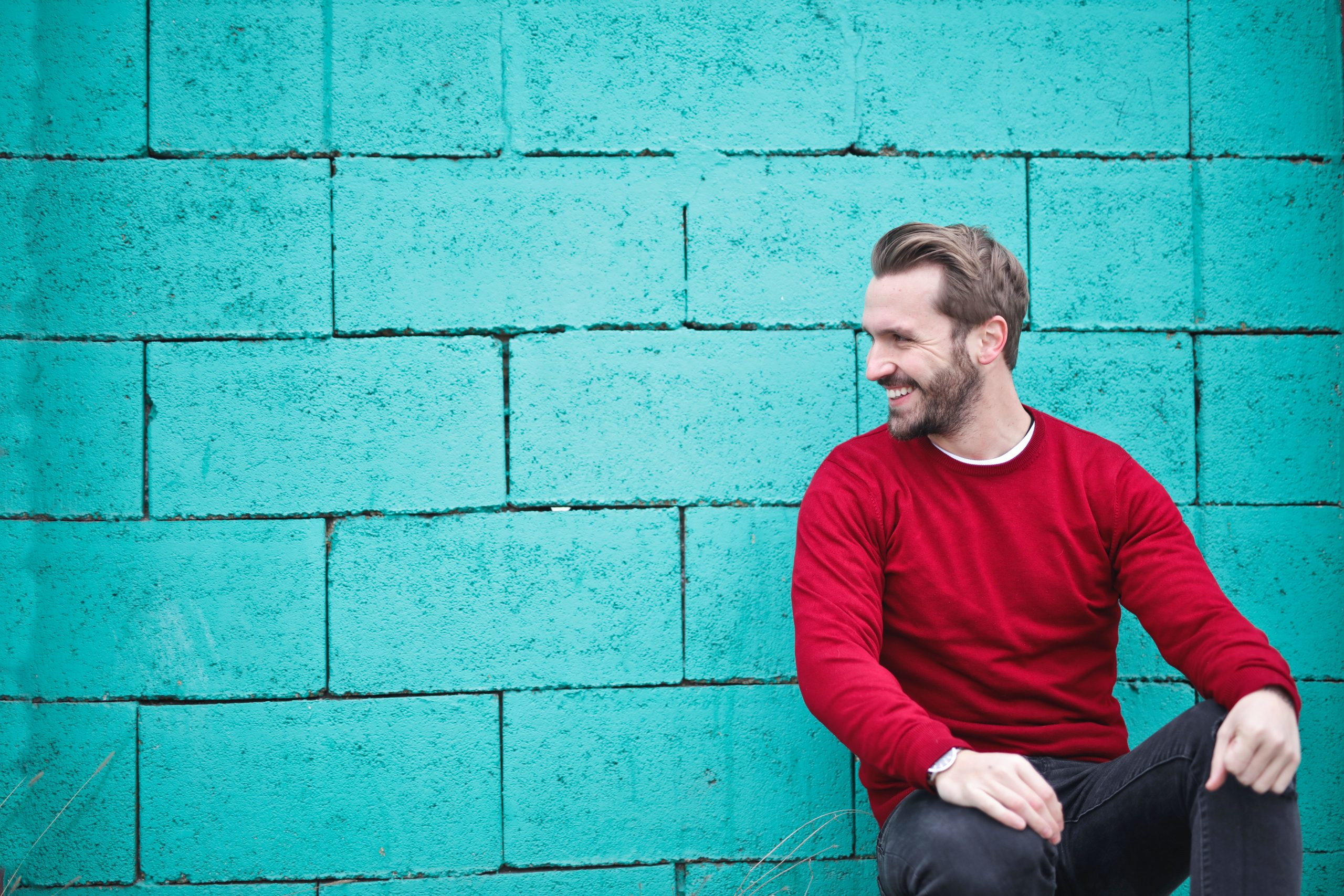 man wearing red top against a blue green brick wall