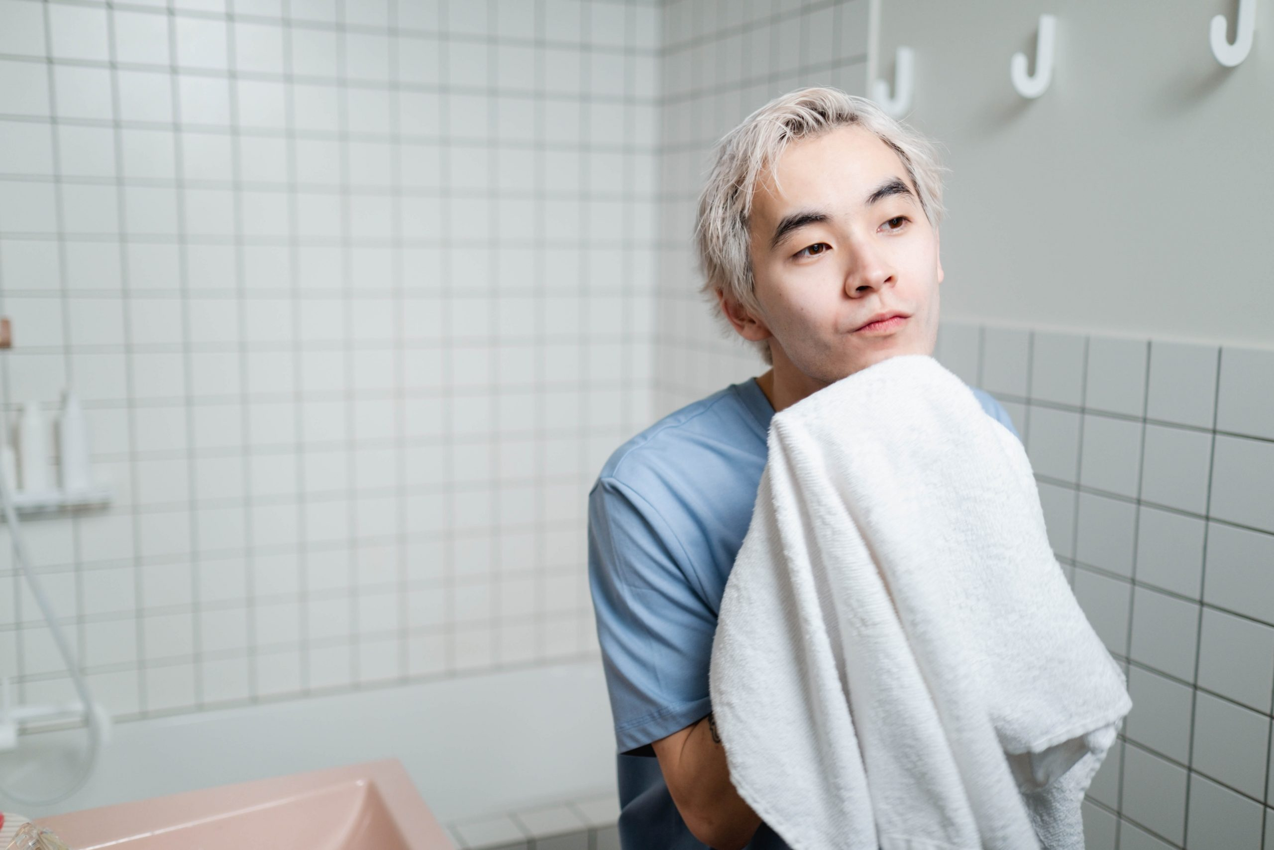 man wiping nose and face with a towel inside a comfort room