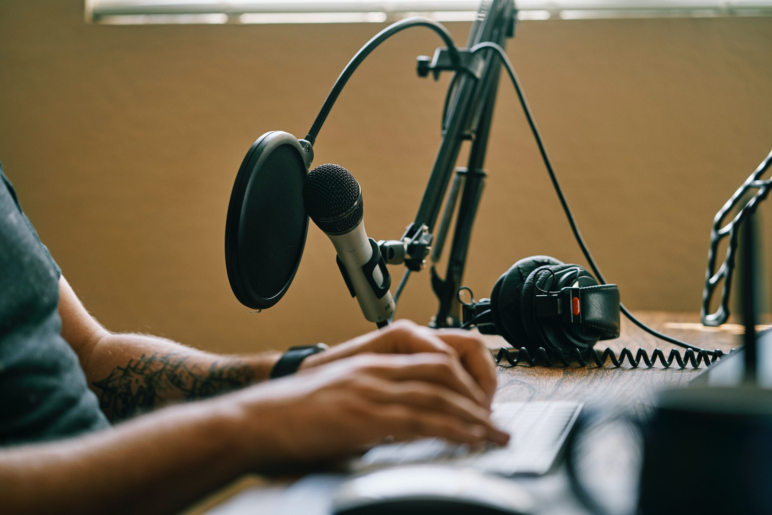 man doing work on a table with his microphone and paper
